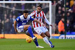 Birmingham City's Che Adams and Stoke City's Ashley Williams compete for possession