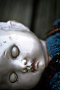 an old and broken doll with closed eyes