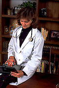 Physician doctor age 46 working on laptop computer in office.  St Paul Minnesota USA