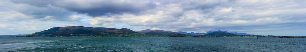 View of the Mourne Mountains from Greenore Harbour, Slievemartin is visible on the left with Knockshee along to the right of the conglomeration of Mountains they are part of; whilst the distinctive shapes of Doan and Slieve Binnian visible in the distance off to the right. The sea and the clouds combine brilliantly to give the impression that they are emanating from the mountains. Image composed of 10 photos at 50mm.<br />
