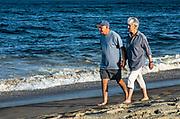 Senior couple walking along the beach.