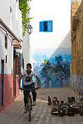Tourists visit and take photos next to street art murals painted on the walls and architecture inside the seaside town during the International Cultural Festival, Asilah, Northern Morocco, 2015-08-10. <br />