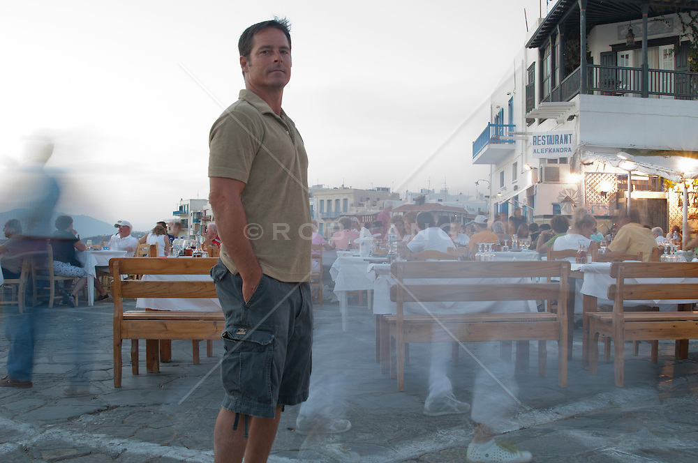 man standing in the town of Mykonons, Greece at dusk