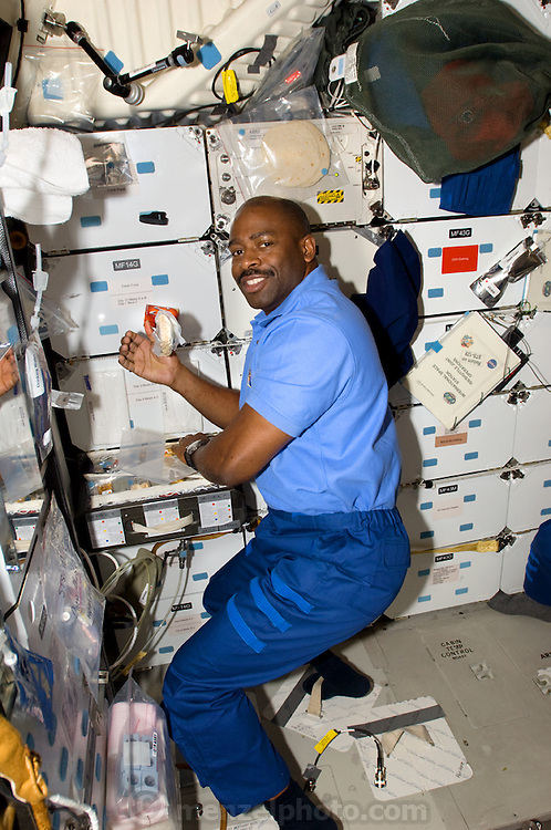 NASA astronaut Leland Melvin, with his feet anchored in loops for stability, retrieves food from his locker in Atlantis galley on board the Space Shuttle Atlantis. (From the book What I Eat: Around the World in 80 Diets.) The caloric value of his day's worth of food in the month of February was 2700 kcals. He is 45; 6' and 205 pounds. MODEL RELEASED.