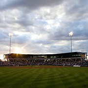The setting sun can be seen through the clouds from behind center field at Citibank Ballpark in Midland, TX as the Midland Rockhounds take on the San Antonio Missions.