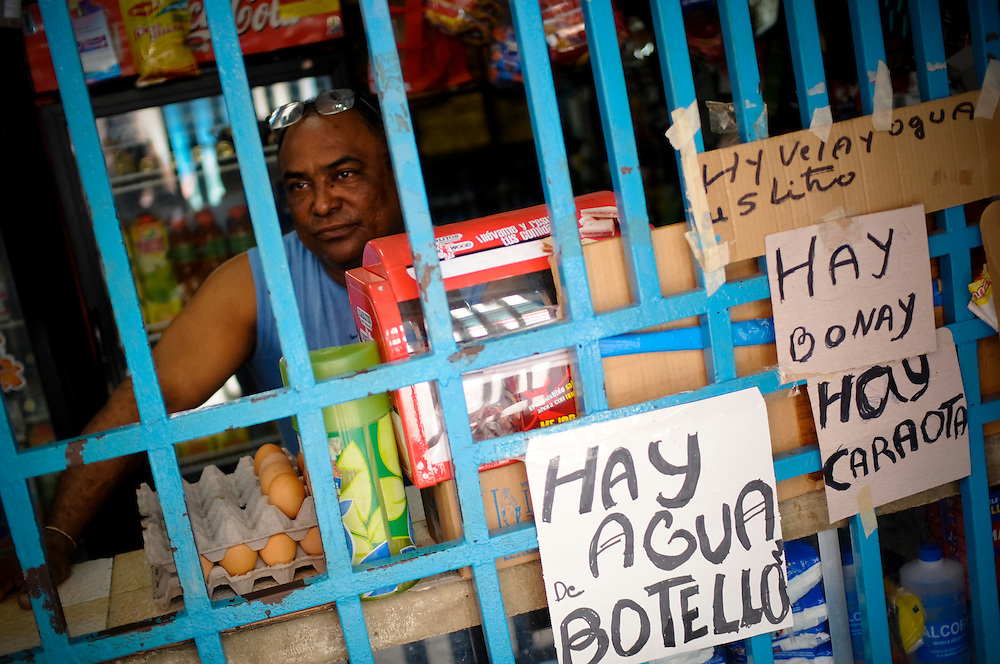 Edgar Luques, 52, owner of a small shop in Petare, a large slum in Caracas Venezuela advertises that he has water and candles, among other things, for sale. Recent government initiated water and electricity rationing have led shop owners to capitalize on the demand for such products.