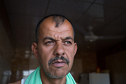 © Licensed to London News Pictures. Hamdaniyah, Iraq. 25/07/2014. Christian refugee Ra'id Samir Kamal (45), formerly a driver in Mosul, stands in the doorway of the home he now shares with 16 other members of his extended family in Hamdaniyah, Iraq. Samir left Mosul on Friday the 18th of July when Islamic State fighters issued an ultimatum to the city's Christian community. When the family left they were forced to pay a tax for their car, their son (19) was threatened at knifepoint to ensure they handed over all of their possessions.<br /> <br /> <br /> Having taken over Mosul Iraq's second largest city in June 2014, fighter of the Islamic State (formerly known as ISIS) have systematically expelled the cities Christian population. Despite having been present in the city for more than 1600 years, Christians in the city were given just days to either convert to Islam, pay a tax for being Christian or leave; many of those that left were also robbed at gunpoint as they passed through Islamic State checkpoints.. Photo credit : Matt Cetti-Roberts/LNP
