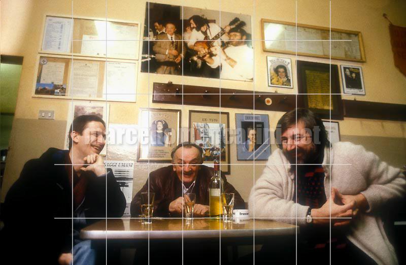 Bologna, 1985. Italian singer-songwriter Francesco Guccini iin a restaurant with two friends / Bologna, 1985 circa. Il cantautore Francesco Guccini in una trattoria con due amici - © Marcello Mencarini