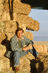 rugged man seated on hay on a ranch