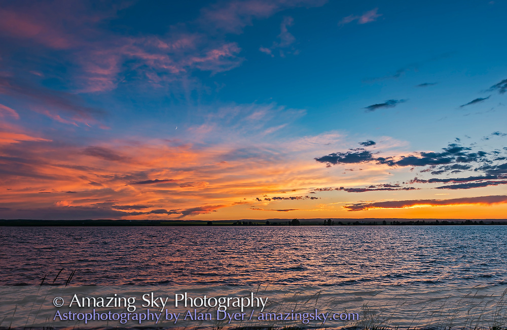 A colourful prairie sunset at MacGregor Lake in southern Alberta, on June 27, 2017, with the waxing crescent Moon amid the clouds. <br /> <br /> This is a frame from a time-lapse sequence, with the 24mm lens and Nikon D750. It serves as a demonstration of a Rule of Thirds composition. Pity it was not a calmer night, for reflections in the water. But the sky was fantastic.
