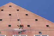 DEN HAAG - Een alpinist is ingezet om de gevels van de karakteristieke torentjes van het ministerie van VWS, schoon te spuiten.  COPYRIGHT GERRIT DE HEUS