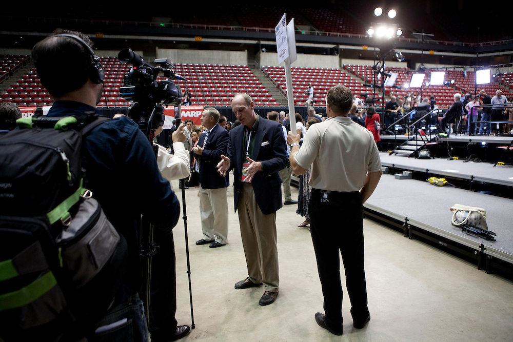 Republican presidential hopeful Thaddeus McCotter, center, talks with a reporter following the Republican presidential debate, in which he did not qualify to participate, on Thursday, August 11, 2011 in Ames, IA.