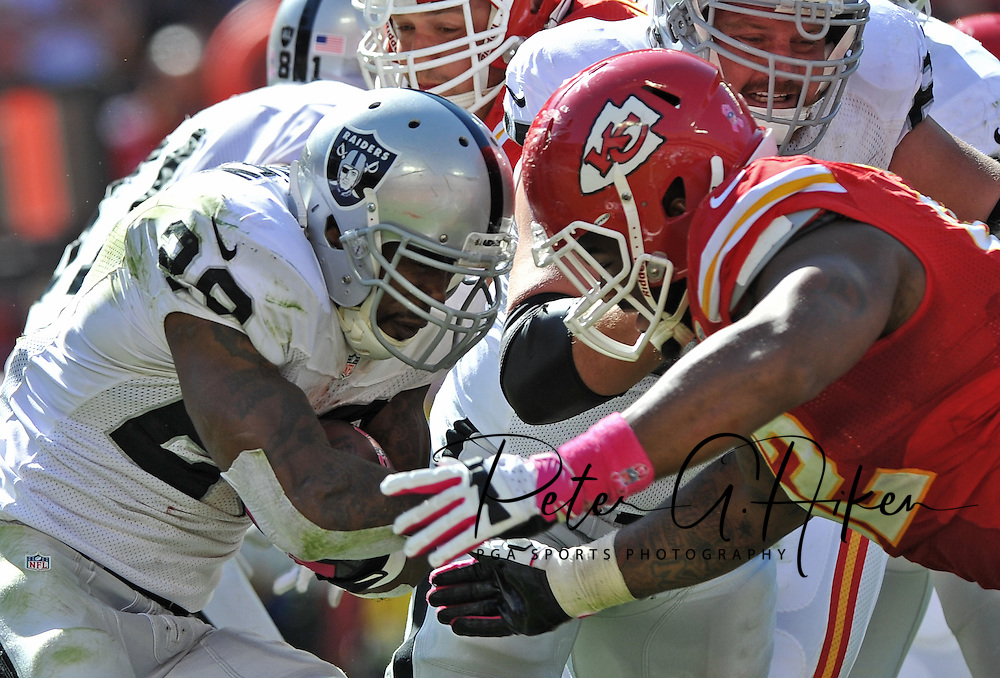KANSAS CITY, MO - OCTOBER 13:  Nose tackle Dontari Poe #92 of the Kansas City Chiefs closes in to tackle running back Darren McFadden #20 of the Oakland Raiders during the second half on October 13, 2013 at Arrowhead Stadium in Kansas City, Missouri.  Kansas City won 24-7. (Photo by Peter Aiken/Getty Images) *** Local Caption *** Dontari Poe;Darren McFadden