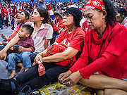 "23 FEBRUARY 2014 - NAKHON RATCHASIMA (KORAT), NAKHON RATCHASIMA, THAILAND: Red Shirt supporters listen to their leadership during a Red Shirt meeting in Korat. The United front of Democracy against Dictator (UDD or Red Shirts), which supports the elected government of Yingluck Shinawatra, staged the ""UDD's Sounding of the Battle Drums"" rally in Nakhon Ratchasima (Korat) to counter the anti-government protests that have gripped Bangkok since November. Around 4,000 of UDD's regional and provincial coordinators along with the organization's core members met at Liptapunlop Hall inside His Majesty the King's 80th Birthday Anniversary Sports Complex in Korat to discuss the organization's objectives and tactics against anti-government protestors, which the UDD says ""seek to destroy the country's democracy."" The UDD leadersa announced that they will march to Bangkok and demonstrate against anti-government protests led by Suthep Thaugsuban.   PHOTO BY JACK KURTZ"