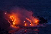 Molten lava streams into the ocean and across roads during the 2016 ocean entry eruption of Puʻuʻōʻō volcano on the big island of Hawaii inside Volcanoes National Park