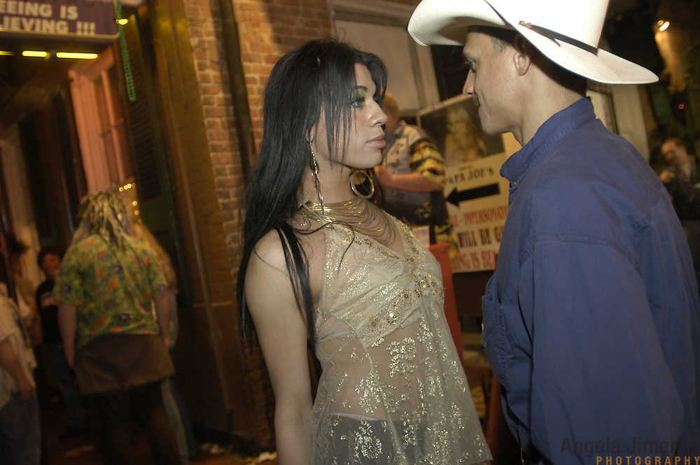 A transsexual woman, left, flirts with a potential customer in front of the Female Impersonators club on Bourbon Street on February 24, 2006 during Mardi Gras in New Orleans, Louisiana. This is the first Mardi Gras since Hurricane Katrina devastated the city.