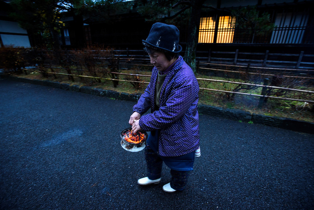 A vendor prepared coals to warm her stall at the morning market in Hida Takayama, Gifu Prefecture, Japan.