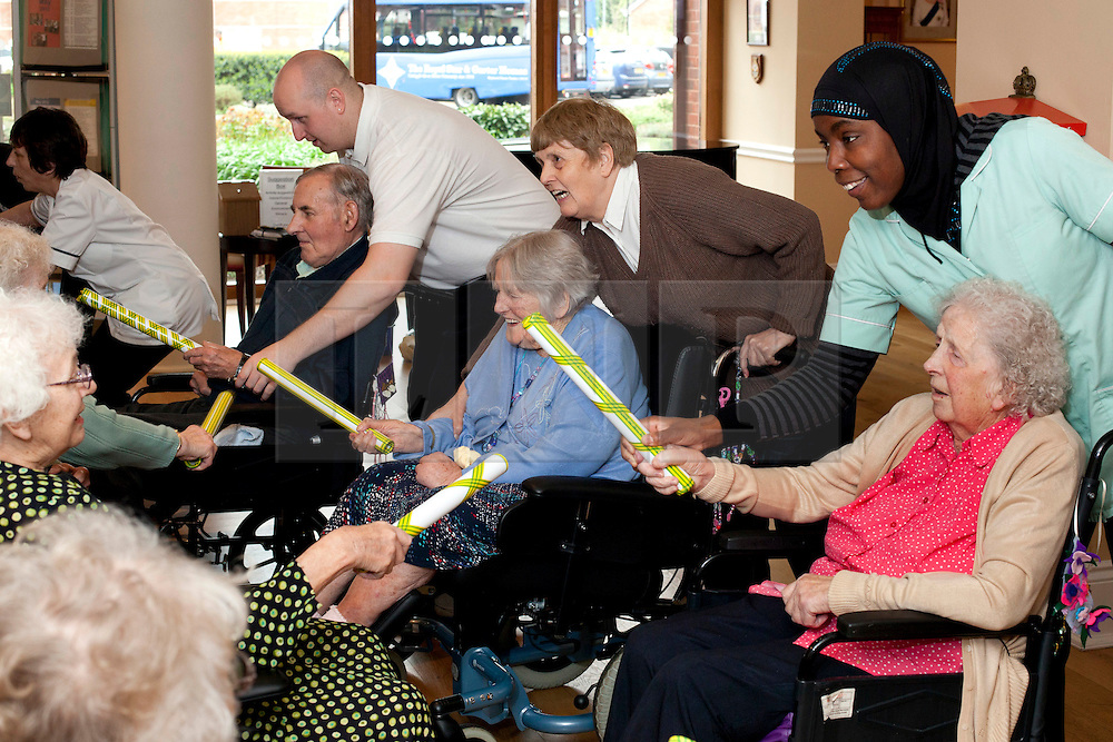 © Licensed to London News Pictures. 6/5/2012. Solihull, West Midlands, UK. Age or disability are no barrier to the residents of The Royal Star & Garter Home in Solihull. Determined to enjoy the May Bank holiday they asked staff if they could organise their own Maypole dance and keep the traddition alive. Streamers were tied to the circular balcony and dropped down to the marquetry floor below, as residents shook bells, waved ribbons and clashed sticks just like Morris men of old. Most of the residents some in their nineties, clapped, cheered and sang as their wheelchairs weaved in and out of the brightly coloured streamers. The Royal Star & Garter is a charity formed in 1916 who care for members of the ex-services and have two homes, one in Richmond and the other, opened in 2008, in Solihull.  Photo credit : Dave Warren/LNP