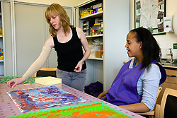 Day Service Officer talking to service user about her painting,