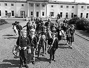 President Hillery Meets Schoolchildren at The Arás.(R59)..1987..15.06.1987..06.15.1987..15th June 1987..As part of an educational tour pupils from Scoil Barra, Ballincollig, Cork were treated to a tour of Arás on Uachtaráin. The pupils were very lucky as the president himself,Dr Hillery, pointed out the highlights of the Arás. With the party was the class teacher Ms Orla Murphy...Image shows the children from Ballincollig and President Hillery taking to the gardens of Arás on Uachtaráin.