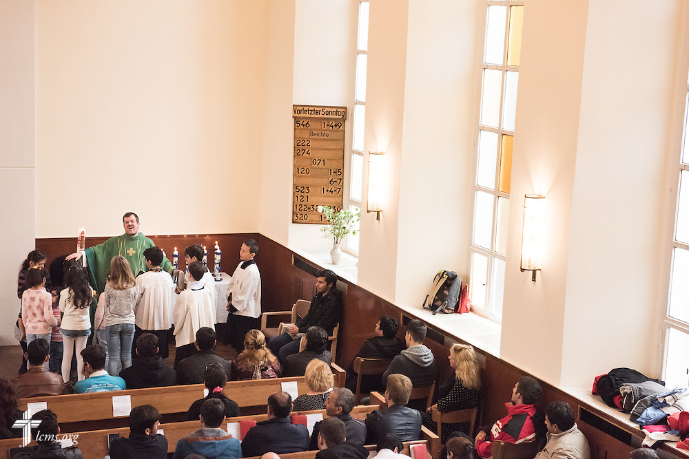 The Rev. Dr. Gottfried Martens baptizes new Christians after they renounced Islam on Sunday, Nov. 15, 2015, at the Dreieinigkeits-Gemeinde, a SELK Lutheran church in Berlin-Steglitz, Germany.  LCMS Communications/Erik M. Lunsford