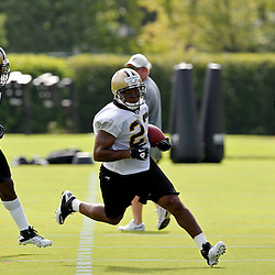 July 29, 2011; Metairie, LA, USA; New Orleans Saints running back Pierre Thomas (23) is pursued by linebacker Jonathan Vilma (51) as defensive coordinator Gregg Williams watches from the sideline during the first day of training camp at the New Orleans Saints practice facility. Mandatory Credit: Derick E. Hingle