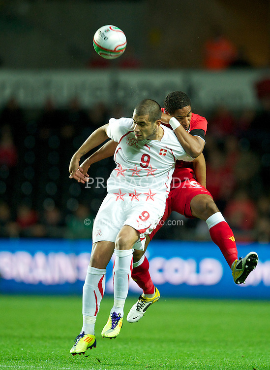 SWANSEA, WALES - Friday, October 7, 2011: Wales' Ashley Williams in action against Switzerland's Eren Derdiyok during the UEFA Euro 2012 Qualifying Group G match at the Liberty Stadium. (Pic by David Rawcliffe/Propaganda)