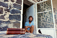 Naturalist, Godfrey Merlen, in his backyard watching darwins finch next to first edition of Darwin's 'Origin of Species', Galapagos Islands