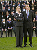 Business couple standing in front of business people sitting in bleachers portrait