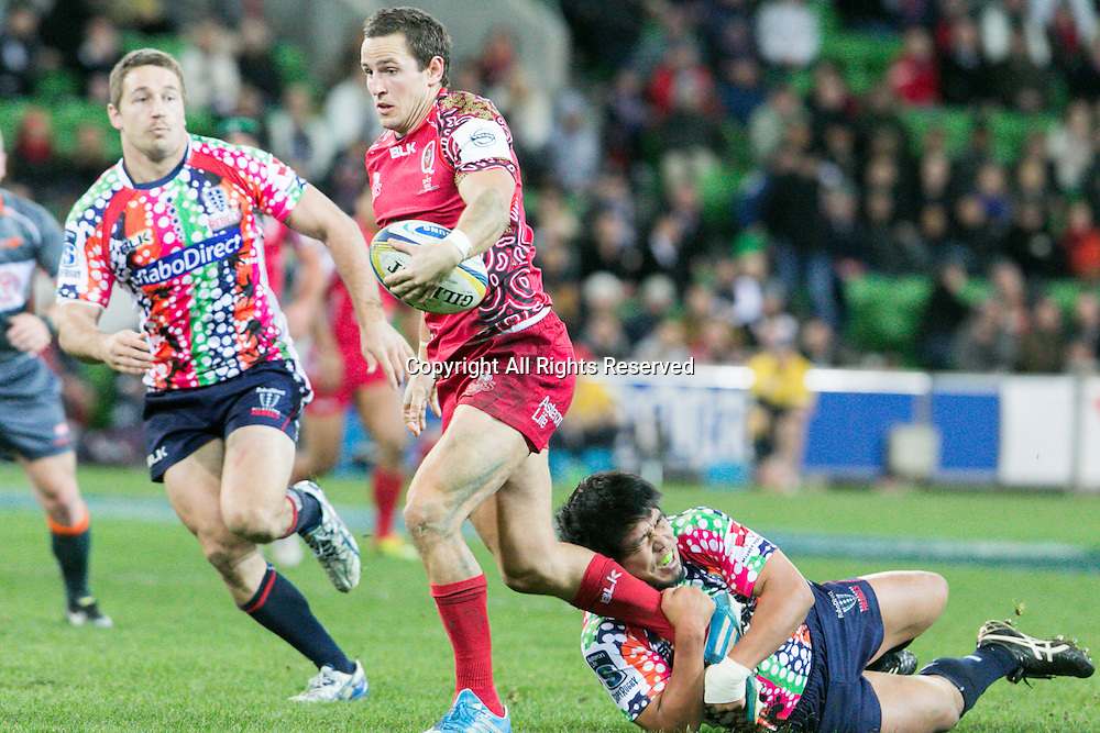 27.06.2014.  Melbourne, Australia.  Super 15 Rugby Union, Melbourne Rebels versus  Queensland Reds. Michael Harris of the Reds gets tackled by Shota Horie of the Rebels