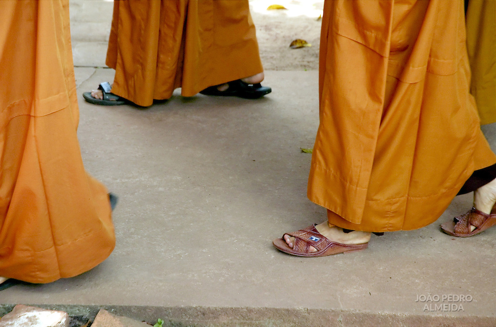Feet of Buddhist monks walking to lunch ceremony