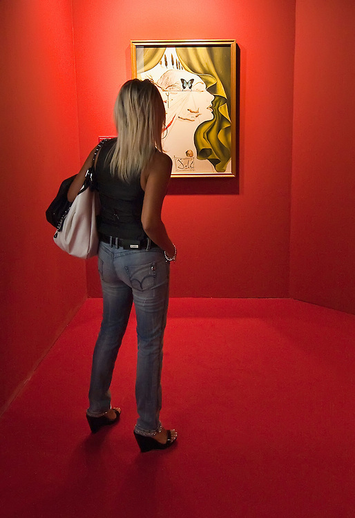 "MILAN, ITALY - SEPTEMBER 21: A womad admires ""Katharina Cornell"", oil painting by Salvador Dali at the Exhibition preview at Palazzo Reale on September 21, 2010 in Milan, Italy. Dali is back in Milan with Il sogno si avvicina, an exhibition that takes place at Palazzo Reale  and that focus on the relationship between the great Spanish artist's visions and his favourite themes:  landscape, dream and desire."