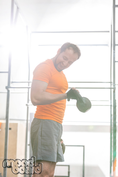 Confident man lifting kettlebell in crossfit gym