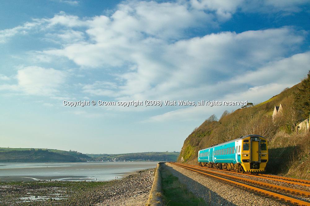 Train near Ferryside<br /> Tywi estuary<br /> Llansteffan in background<br /> Swansea to Carmarthen line<br /> Arriva Trains Wales<br /> Rail<br /> Transport