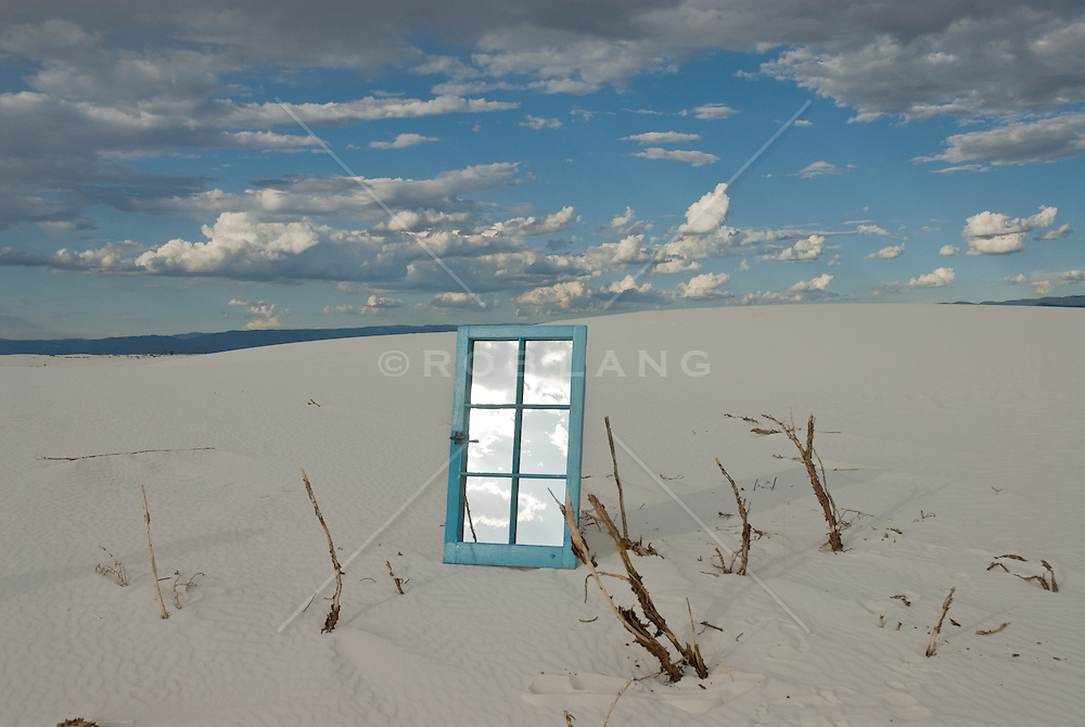 Mirrored window frame and branches in a sand dune in White Sands National Park, NM
