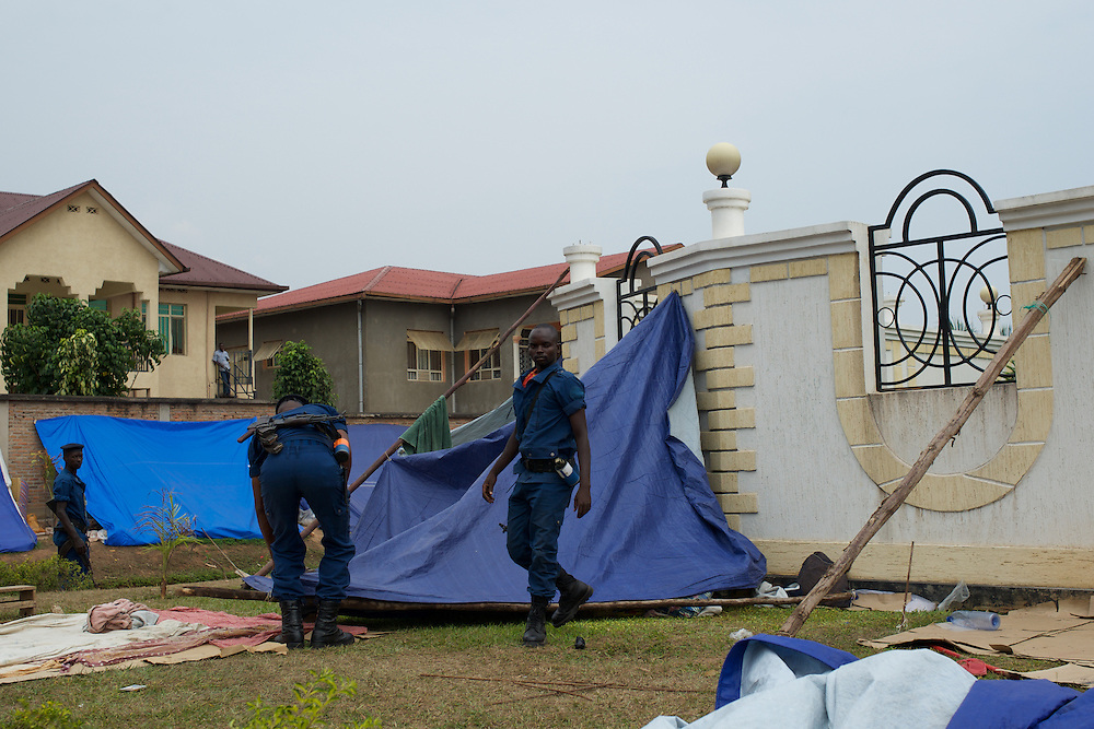 """Burundian police dismantle the improvised camp of the university students seeking shelter outside the US embassy in Bujumbura, minutes after hundreds of students storm the embassy grounds seeking refuge. The students moved to the area in early May because, they claim, the US authorities ensure their security, after their university was closed amid anti-government protests. The government closed the university at the end of April, citing """"insecurity""""."""