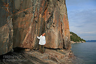 Woman admires centuries-old Ojibwe pictographs at Agawa Rock in Lake Superior Provincial Park, Ontario; Canada.