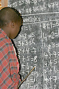 Africa, Tanzania, Lake Eyasi, young Maasai child learns arithmetic in a school room. An ethnic group of semi-nomadic people February 2006