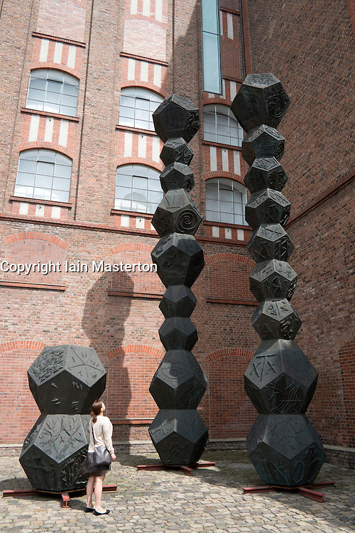 Woman looking at sculptures outside at Kuppersmuhle Museum in Duisburg Germany