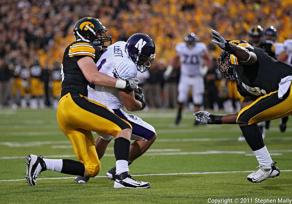 October 15, 2011: Northwestern Wildcats wide receiver Jeremy Ebert (11) is pulled down by Iowa Hawkeyes linebacker Tyler Nielsen (45) during the first half of the NCAA football game between the Northwestern Wildcats and the Iowa Hawkeyes at Kinnick Stadium in Iowa City, Iowa on Saturday, October 15, 2011. Iowa defeated Northwestern 41-31.