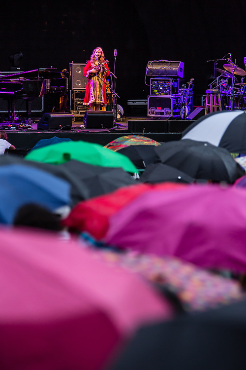 3 August 2017 – Brooklyn, NY. Singer Nellie McKay opened for Béla Fleck and the Flecktones to a large crowd at the BRIC Celebrate Brooklyn! Festival at the Prospect Park Bandshell. Nellie McKay performing before an audience covered by umbrellas during a brief shower.