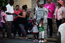 SSG Kellen Phillips watches the parade with great-niece Ne'Keya Fraser and son Jaylen Phillips.  Veteran's Day Parade and Program at the Frankliin Delano Roosevelt Memorial Park in Charlotte Amalie.  St. Thomas.  11 November 2013.  © Aisha-Zakiya Boyd