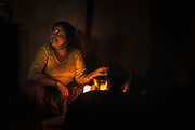 Grandmother Laxmi Phuyal tends to the fire where she cooks for her family. The fire provides heat for boiling and frying all the family's meals, which often include rice, lentils, curry and vegetables.