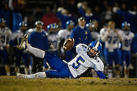 JEROME A. POLLOS/Press..Coeur d'Alene High quarterback Ryan Dunton slips and falls to the turf after taking the snap in the second half Friday in the cross-town rivalry game against Lake City.