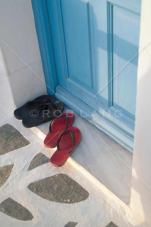 two pair of flip flops outside a door in Greece