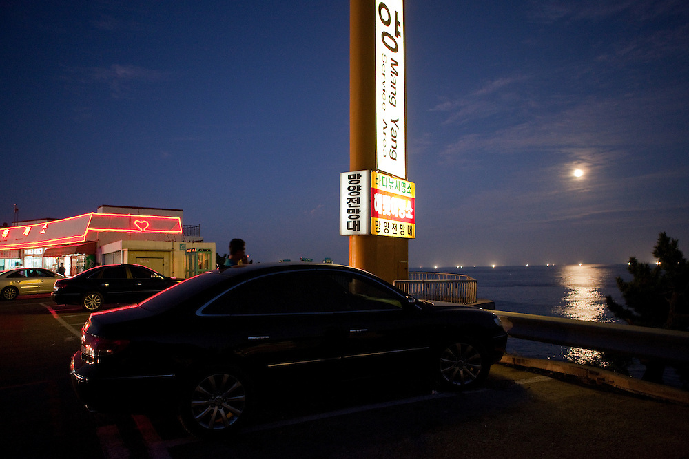Mangyang rest area with parked cars, shops and advertisiment board in full moon light / South Korea, Republic of Korea, KOR, 04 October 2009.
