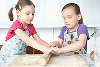 Two girls (5-6) rolling dough