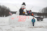 Ellen Daniel (bottom) of Petoskey stands in front of the 20 foot tall Snowman that her grandchilden and their friends (left to right) Josh Daniel, Buddy Gray, Kyle Green, Leslie Green, Abby Gray, Brooke Tracy, Kayla Daniel and Kenny Reame helped build on her U.S. 131 property.
