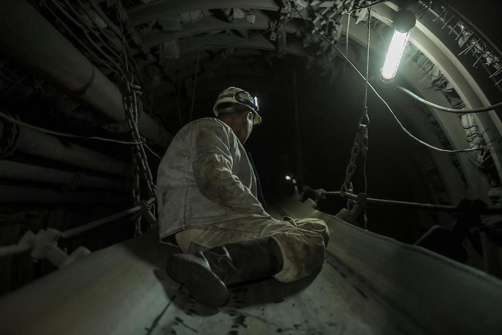 A miner lies on a conveyor belt that he will ride part of the way from the coal face 1300 meters underground to the surface at the Shcheglovskaya Coal Mine on Friday, March 25, 2016 in Makiivka, Ukraine.