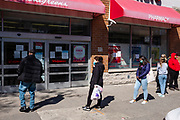 Brooklyn, NY - 26 March 2020. Residents of New York City have been asked to stay home as a result of the novel coronavirus, and all but essential businesses have been asked to close. In Brooklyn's Midwood neighborhood, many businesses have their shutters rolled down, and the few that are open limit the number of people who can enter. Patrons, some of whom wear face masks and surgical gloves, stay well apart as they wait to enter a Walgreen's pharmacy on Avenue J.
